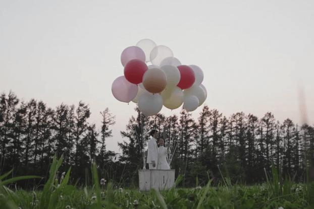 風船で飛ぶ気球に乗るカップル
