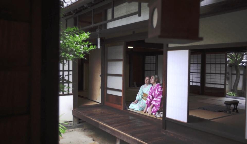 日本家屋の軒下に座る和装の海外女性