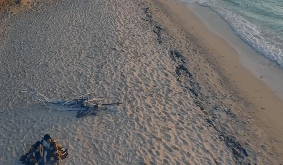 夕日が沈む浜辺で過ごすカップル
